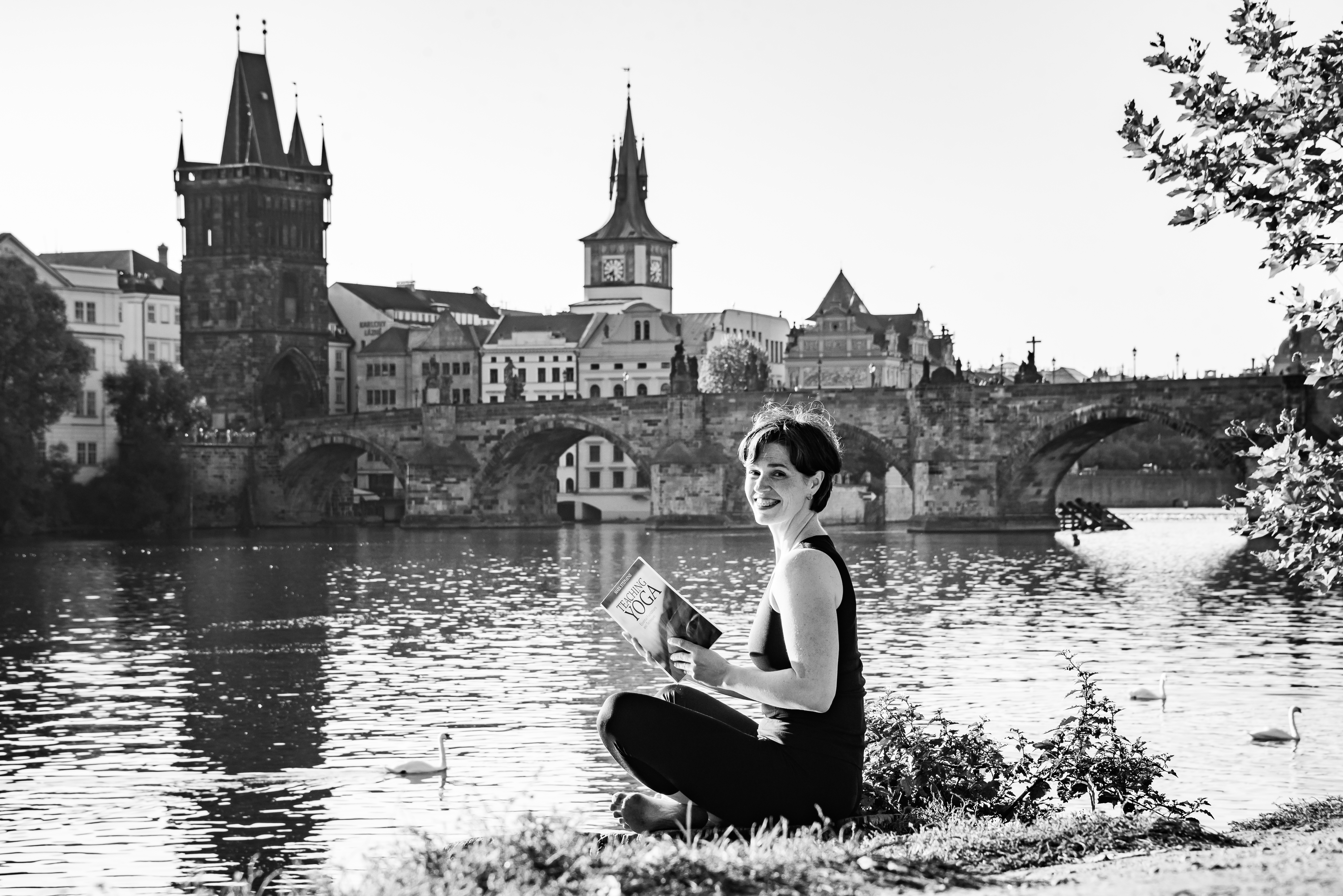 a woman sitting at the river, reading a book