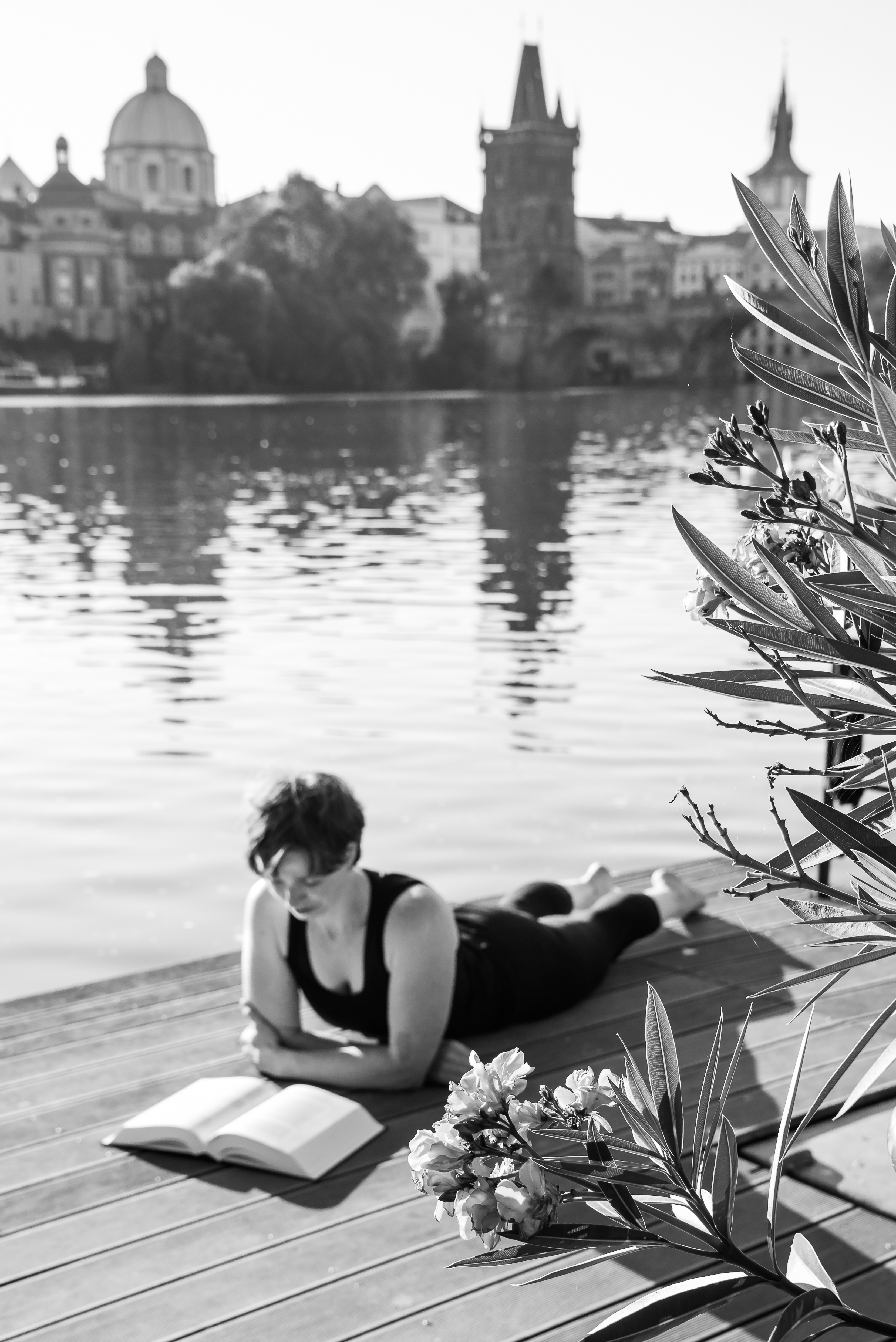 woman laying on the bank of the river reading a book